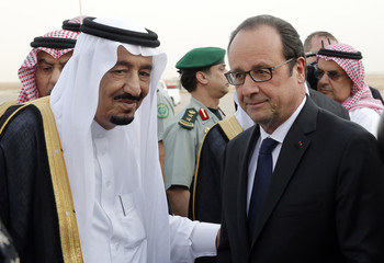 French President Hollande is greeted by Saudi Arabia's King Salman upon his arrival at Riyadh airport