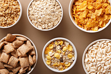 Bowls of various cereals view from above. Corn flakes, oat flakes, muesli, granola assortment. Top view