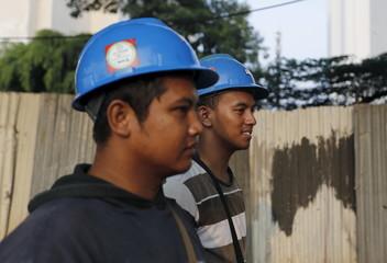 Construction workers walk in Sudirman business district in Jakarta
