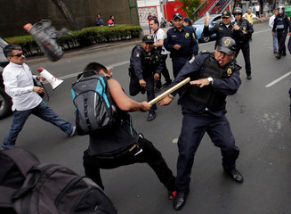 Riot police clash with a protester during a demonstration against bullfights outside a bullring in Mexico City