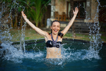 Horizontal portrait of attractive laughing girl in black bikini standing in pool and splattering water with her hands, house and palm tree on background