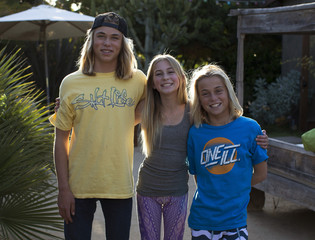 Twelve-year-old yoga instructor Jaysea DeVoe poses for a picture with her twin brother Fisher and older brother Ryder in Leucadia, California