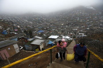 Concepcion Cuya (L) and her mother Elisa Inga carry a bag containing fish donated by a private businessman, at Pamplona Alta, a shanty town in San Juan de Miraflores, on the outskirts of Lima