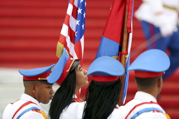 Honor guards carry the U.S. and Cuban flags as they stand at the bottom of the stairs of the Revolution Palace during a visit by U.S. President Barack Obama in Havana