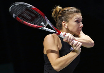Simona Halep of Romania hits a return to Serena Williams of the U.S. during their WTA Finals singles tennis match at the Singapore Indoor Stadium