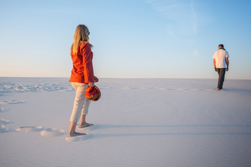 Man and a young beautiful woman go one by one in the desert