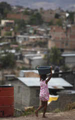 A girl carries a bucket of water after collecting it from a government truck in the Las Vegas neighbourhood of Tegucigalpa