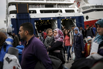 Refugees and migrants arrive aboard the passenger ferries Blue Star Patmos and Eleftherios Venizelos from the islands of Lesbos and Chios at the port of Piraeus