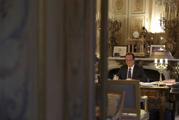 French President Francois Hollande works in his office during a photo session at the Elysee Palace in Paris