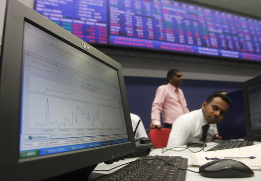 A broker is pictured near a computer screen showing movements in the stock market since the morning opening at the Colombo Stock Exchange