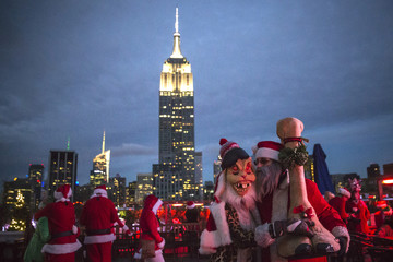 The Empire State Building is seen in the background as revelers taking part in SantaCon are pictured at a top a rooftop bar after sunset in Midtown Manhattan