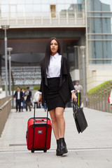 businesswoman with trolley bag walking in urban environment