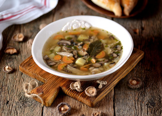 Mushroom soup with potatoes, carrots, onions and chicken meat on an old wooden background. Rustic style.