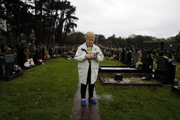 Margaret McKinney holds a running shoe, which her son Brian was wearing when his body was found, as she stands by his grave in Milltown cemetery in West Belfast