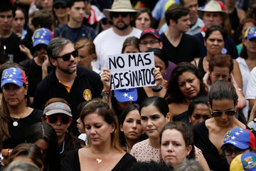"""A placard that reads """"No more murders"""" is seen during a tribute to Miguel Castillo, who died during a protest against Venezuelan President Nicolas Maduro, in Caracas"""