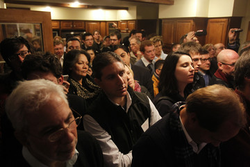 People listen to U.S. Republican presidential candidate Huntsman during a campaign event in Bedford