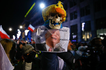 Anti-government activists march through Warsaw during a demonstration to mark the 35th anniversary of the marshal law in Poland