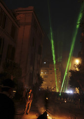 Protesters opposing Egyptian President Mursi shine laser pointers at riot police during clashes in Cairo