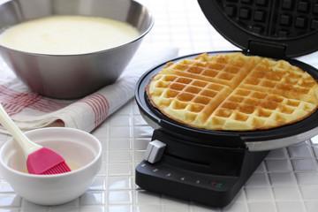 preparing homemade waffles by waffle maker machine.