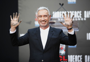 Director Roland Emmerich displays his hands after placing them into the cement during his Hand and Foot Print Ceremony in Hollywood