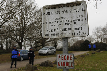 French gendarmes secure the access to a pond after an unidentified body was discovered in Lavau-sur-Loire, western France