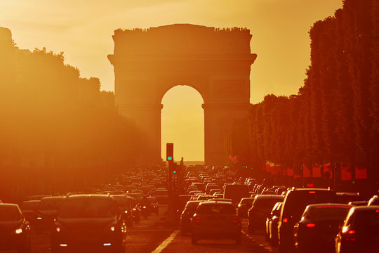 Traffic jam with lots of vehices in Paris on Champs-Elysees street with Triumphal Arch
