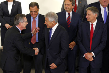 Thomas de Maiziere shakes hands with Chuck Hagel while Philip Hammond looks on during a NATO defence ministers meeting at the Alliance headquarters in Brussels