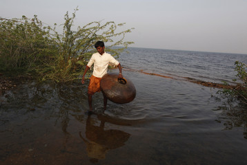 Youth walks with a floating pitcher, which he uses to catch fish in Soneri village next to Keenjhar Lake, near Thatta