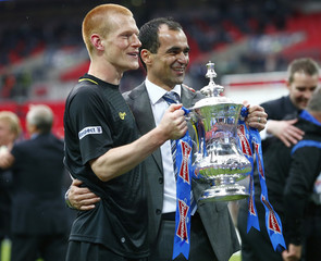 Wigan Athletic's manager Roberto Martinez holds the trophy with goalscorer Ben Watson after defeating Manchester City in their FA Cup final soccer match at Wembley Stadium in London