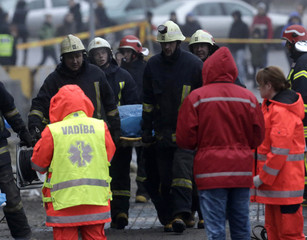 Firefighters move a body from a collapsed supermarket in Riga