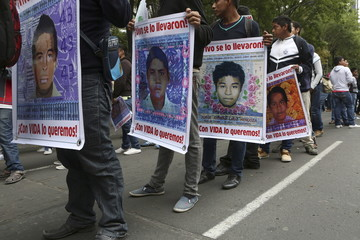 Demonstrators carry posters with photos of some of the 43 missing students from Ayotzinapa College Raul Isidro Burgos during a march to mark the 16-month anniversary of their disappearance in Mexico City