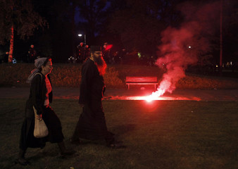 An Orthodox church priest and a woman walks by flares thrown during a protest against the arrest of Ratko Mladic in Belgrade