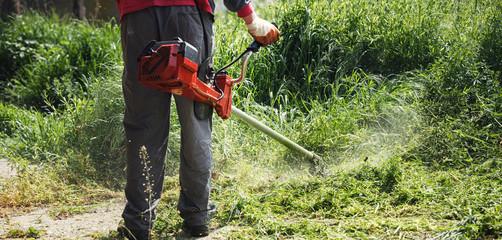 mowing trimmer - worker cutting grass closeup.