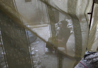 A Free Syrian Army fighter is seen through a curtain as he sits along a street in Deir al-Zor