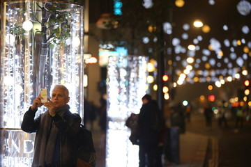 Man takes a picture on Oxford street after Australian singer Kylie Minogue turned on the Christmas lights, in London