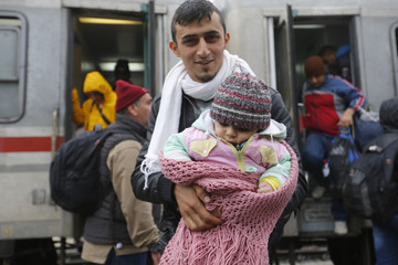 Migrants set off on foot to the border with Hungary after arriving by train at Botovo
