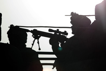 U.S. Marines from Bravo Company of the 1st Battalion, 6th Marines, scan the area during an operation in the town of Marjah