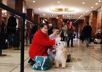 Patricia Princehouse pets her dog Brio, a Pyrenean Shepherd breed, inside the Pennsylvania Hotel in New York