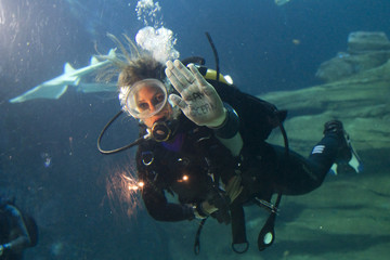 """French sailor and UNESCO Ambassador for the Oceans Fontenoy shows a message written on the palm of her hand as she dives with sharks during the opening of the exposition """"Meet The Sharks"""" at the Aquarium of Paris"""