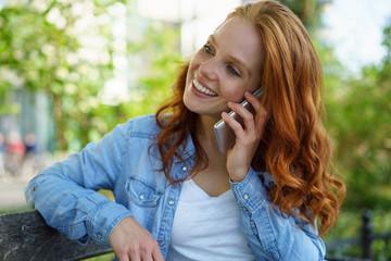 frau sitzt draußen im park und telefoniert mit ihrem handy