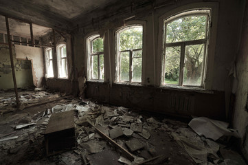 A large destroyed hall in a kindergarten in Chernobyl: garbage on the floor, inverted furniture, torn wallpaper, dusk in the room, sunshine, green trees, spring in Ukraine.