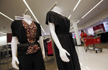 An employee at a new CityTarget store pushes a shopping cart past some display mannequins as they prepare for the shop's opening in downtown Chicago