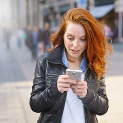 frau geht durch die stadt und schaut überrascht auf ihr mobiltelefon
