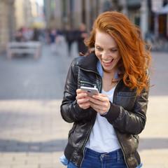 frau steht in der stadt und liest lachend eine nachricht auf ihrem mobiltelefon