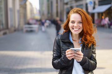lachende frau steht in der einkaufsstraße und hält ihr handy in der hand