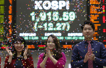 Employees of the Korea Exchange pose in front of the final stock price index during a photo opportunity for the media at the ceremonial closing event of the 2014 stock market at the Korea Exchange in Seoul