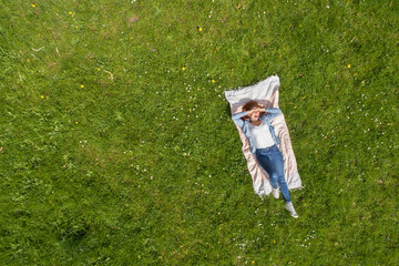 frau liegt entspannt im park auf einer decke