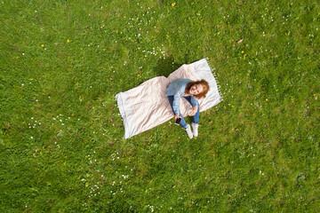 frau sitzt im park auf einer decke und hält ihr mobiltelefon in der hand