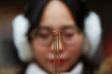 A woman holds incense sticks while praying at Yonghegong Lama Temple on the first day of the Lunar New Year of the Rooster in Beijing