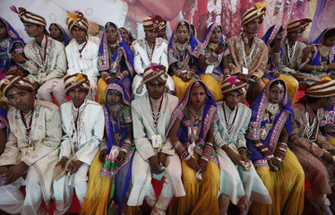 Brides and grooms pose for pictures during a mass wedding ceremony at Ramlila ground in New Delhi